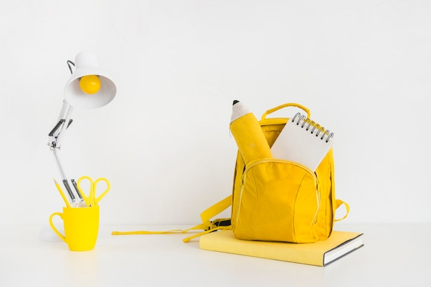 Stylish teenage workspace with yellow backpack and reading lamp Free Photo