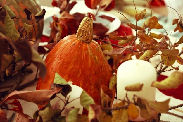 カボチャと乾燥した枝のあるスタイリッシュな感謝祭の秋のテーブルの装飾 Premium写真