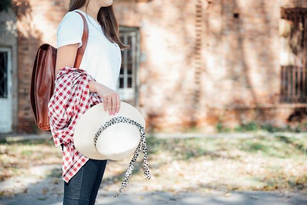 Stylish traveler with vintage backpack holding hat Free Photo