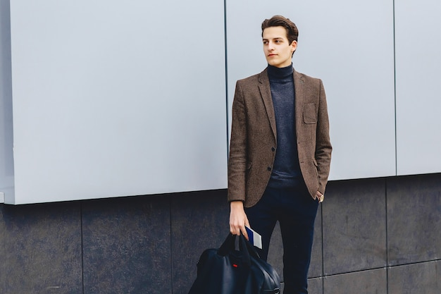 Stylish traveller in jacket with passport and tickets in urban context Premium Photo