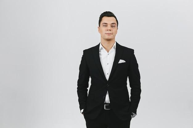 세련된 트렌디 한 젊은 갈색 머리 남자는 흰색 셔츠와 흰색 배경에 검은 색 정장 프리미엄 사진