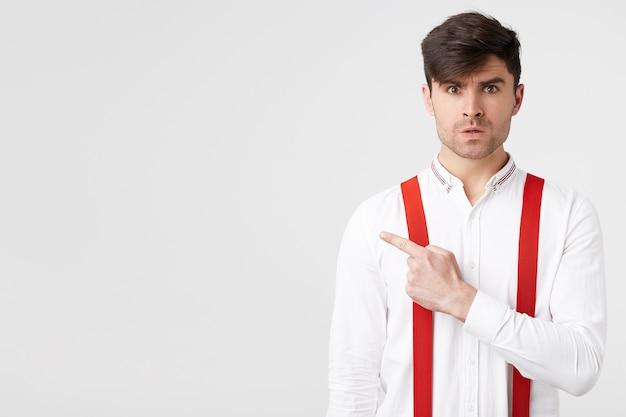 Un ragazzo dai capelli scuri con la barba alla moda si risente con l'espressione del viso indignata, indicando con il dito indice verso il lato sinistro Foto Gratuite