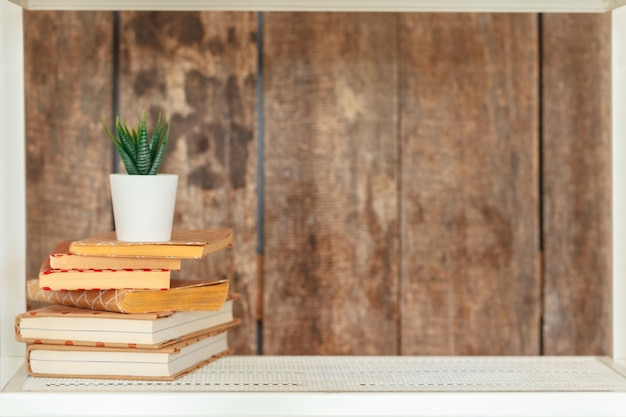 Stylish white bookshelf against grunge wooden wall Premium Photo