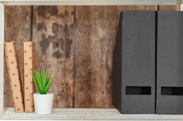 Stylish white bookshelf against grunge wooden wall Premium Photo