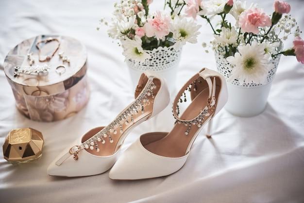 Stylish white wedding bridal shoes, perfume, flowers and jewelry. Premium Photo