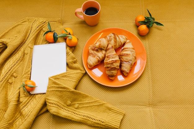ニットのセーター、クロワッサン、クレメンタイン、テーブルの上のノートの上からオレンジ色のスタイリッシュな冬のイメージ 無料写真