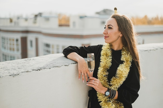 Stylish woman in black dress with a glass of champagne Free Photo