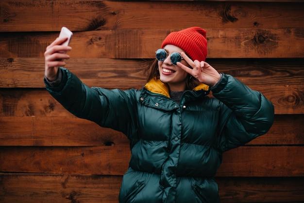 Стильная женщина-блогер в ярком разноцветном наряде делает селфи на деревянной стене Бесплатные Фотографии