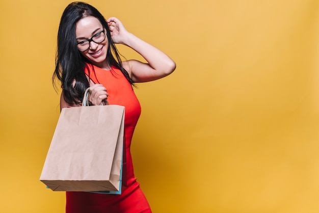 Stylish woman in dress with shopping bags Free Photo