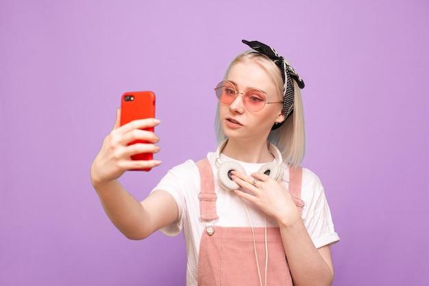헤드폰과 밝은 옷을 입은 세련된 여성이 스마트 폰에서 셀카를 만듭니다. 프리미엄 사진
