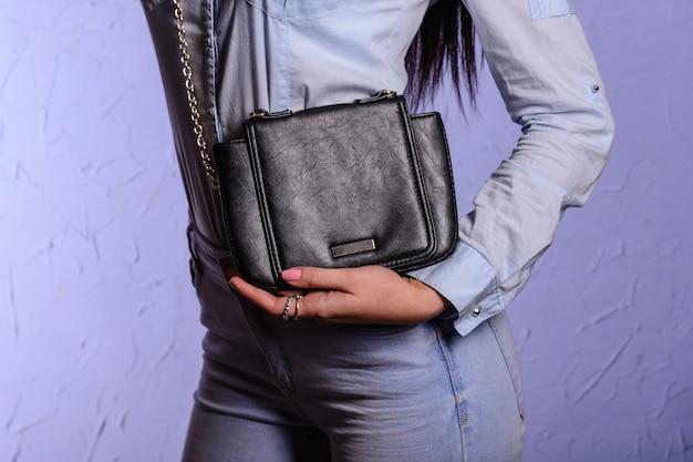 작은 검은 핸드백 클러치와 청바지에 세련 된 여자 프리미엄 사진