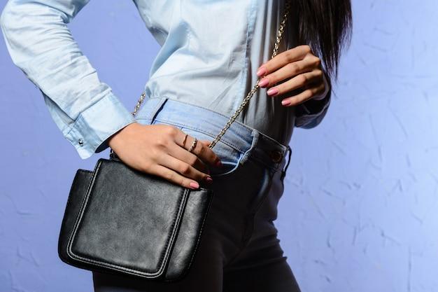 작은 검은 핸드백과 청바지에 세련 된 여자 프리미엄 사진