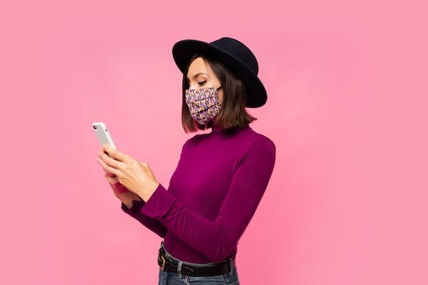보호 마스크와 휴대 전화를 사용 하여 서있는 검은 모자에 세련 된 여자. 무료 사진