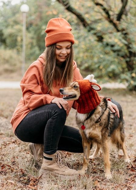 Donna alla moda a fare una passeggiata con il suo cane Foto Gratuite