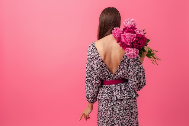 Stylish woman on pink background in summer trendy dress posing with peony flowers bouquet, view from back, sexy outfit Free Photo
