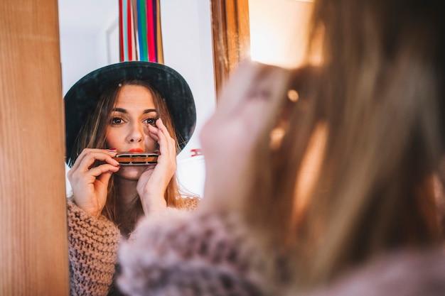 Stylish woman playing harmonica Free Photo