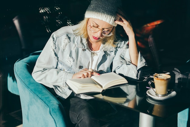 Stylish woman reading in cafe Free Photo