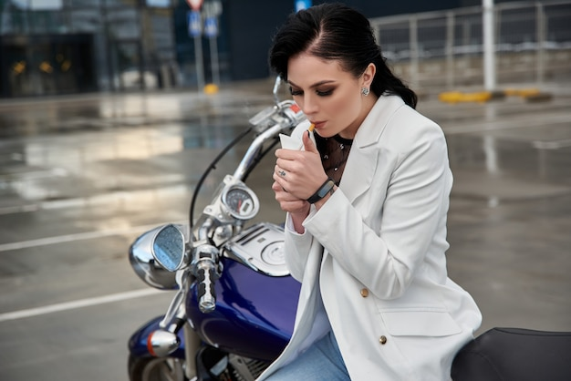 Stylish woman sits on a motorcycle and smokes a cigarette in the parking lot near the shopping center. Premium Photo