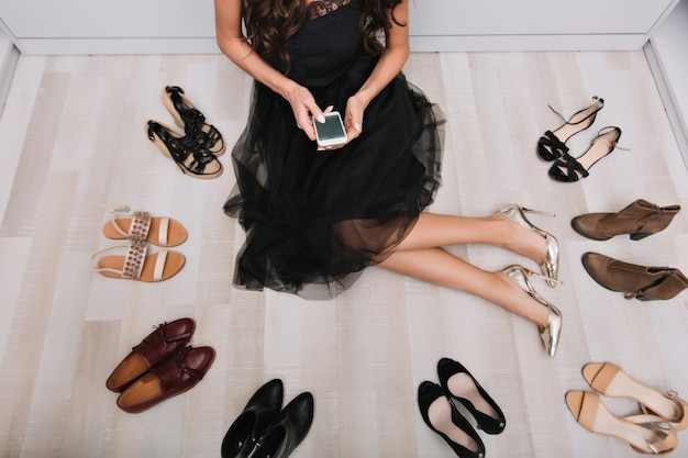 Stylish woman sitting on the floor in wardrobe with smartphone in hands, writing message, surrounded by lot of shoes. she wearing black fluffy skirt and silver luxury shoes. Free Photo