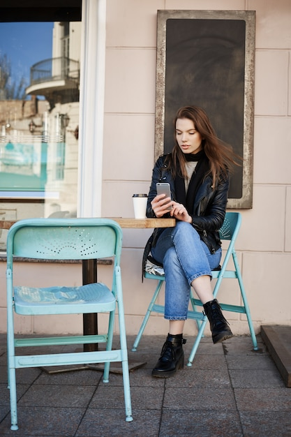Stylish woman sitting in patio of restaurant, drinking coffee and making appointment to cosmetologist via internet, holding smartphone and typing Free Photo