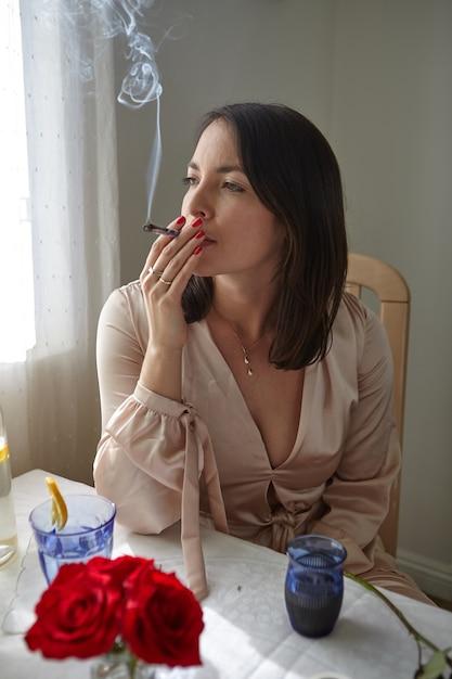 Стильная женщина курит косяк дома Бесплатные Фотографии
