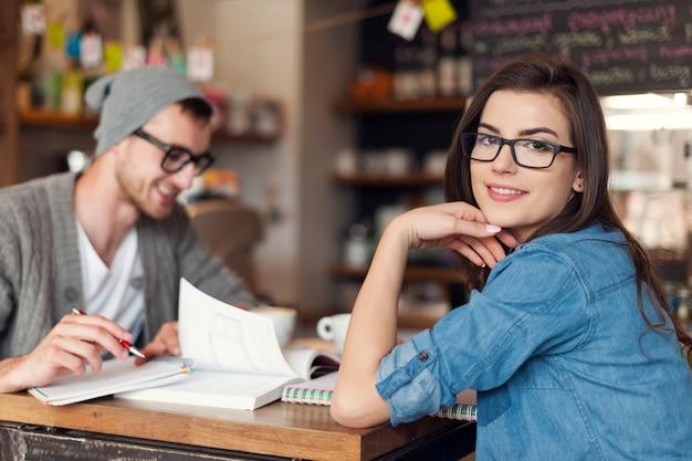 Donna alla moda che studia con la sua amica al caffè Foto Gratuite