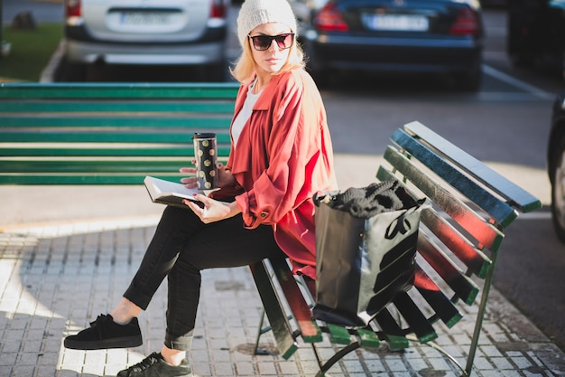 Stylish woman with book and cup Free Photo