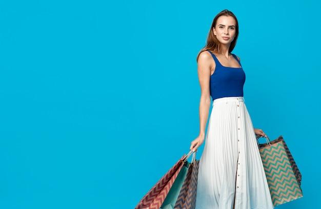 Стильная женщина с хозяйственными сумками Premium Фотографии