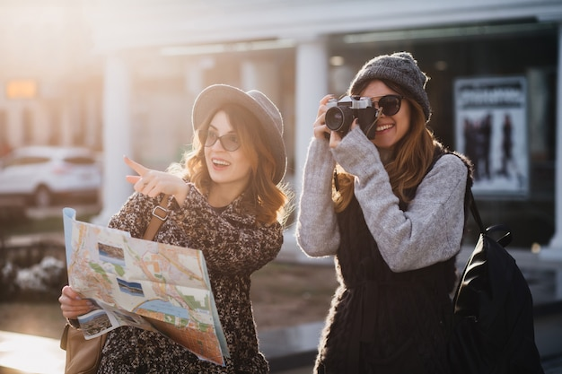 Stylish women spending time outdoor in cold day exploring new places with camera. gorgeous female photographer walking around city with sister which pointing with finger away and smiling holding map. Free Photo
