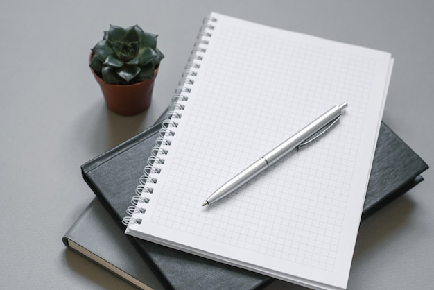 Стильное рабочее место. блокноты и дневники на сером рабочем столе с ручкой, сочные. Premium Фотографии