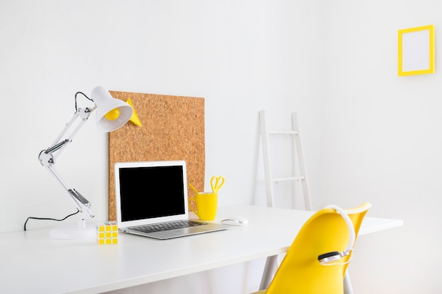 Stylish workspace with cork board and yellow chair Free Photo