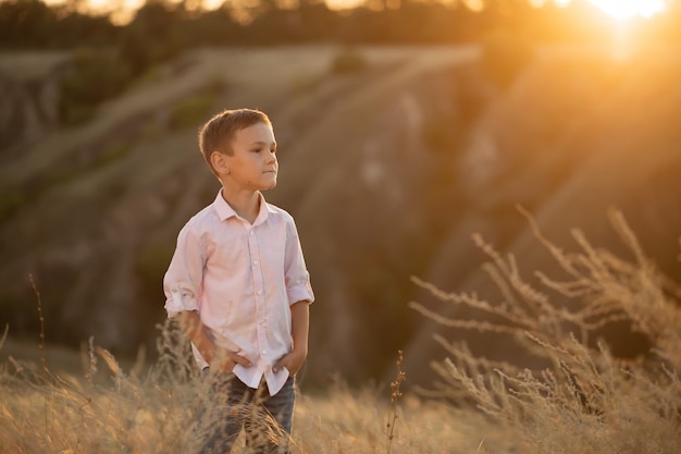 Stylish young boy posing in field at sunset Premium Photo