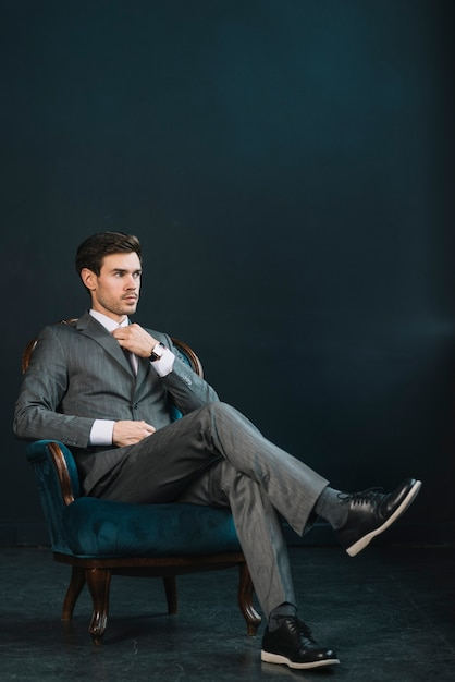 Stylish young businessman sitting on armchair against dark background Free Photo