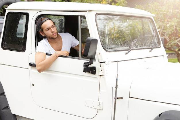 彼の白いスポーツユーティリティ車の開いているウィンドウを探しているスタイリッシュな若い白人男。野球帽をかぶったひげを剃っていない男性がジープを後方に運転し、ロードトリップを楽しんでいます 無料写真