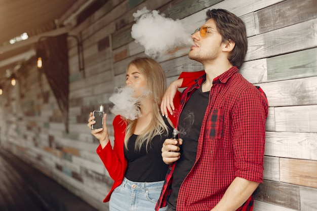 Stylish young couple with vape in a city Free Photo