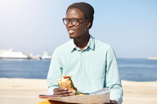 Elegante giovane sognatore con mappa seduto sull'argine contro il mare calmo Foto Gratuite