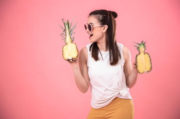 Стильная молодая девушка в солнечных очках улыбается и держит фрукты на розовой стене. концепция летних каникул. Premium Фотографии