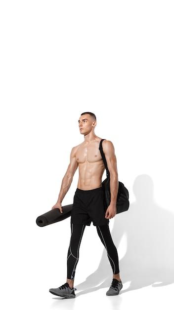 흰색 스튜디오 배경, 그림자와 초상화에 연습 세련 된 젊은 남자 선수. 스포티 한 핏 모델은 모션과 액션에서 작동합니다. 바디 빌딩, 건강한 라이프 스타일, 스타일 컨셉. 무료 사진
