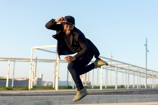 Stylish young male dancer in fashionable black clothes dancing on a street in the city on an autumn afternoon Premium Photo