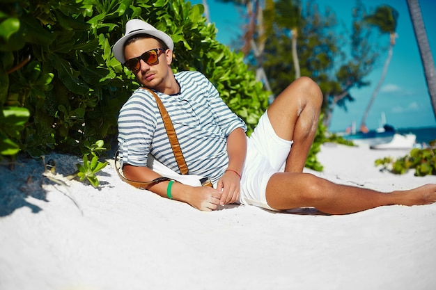 Stylish young male model man lying on beach sand wearing hipster summer hat Free Photo