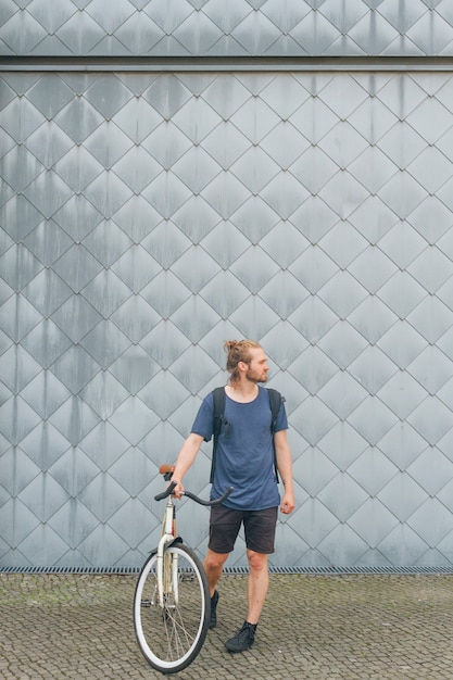 Stylish young man carrying backpack standing with his bicycle Free Photo