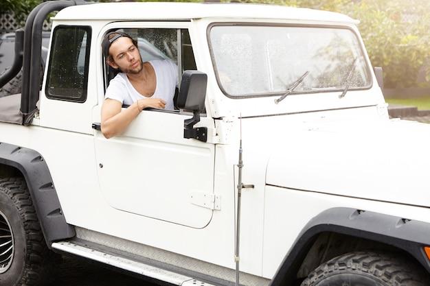 白い四輪駆動車を運転するスタイリッシュな若い男 無料写真