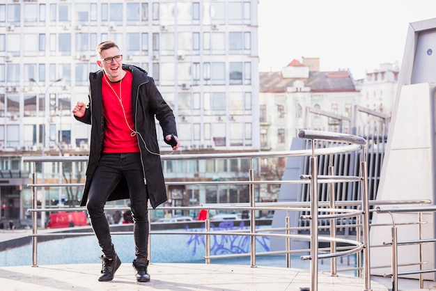 Stylish young man listening music on earphone dancing at outdoors Free Photo