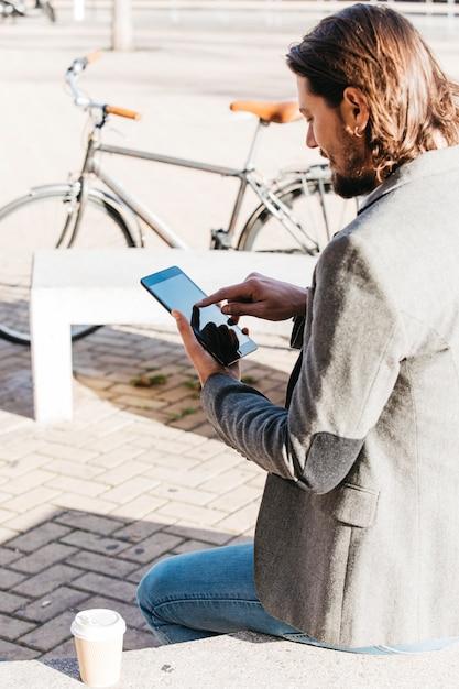 Стильный молодой человек сидит на скамейке с чашкой кофе на вынос с помощью мобильного телефона Бесплатные Фотографии