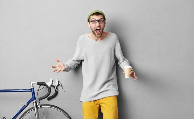 Стильный молодой человек, стоящий возле велосипеда Бесплатные Фотографии