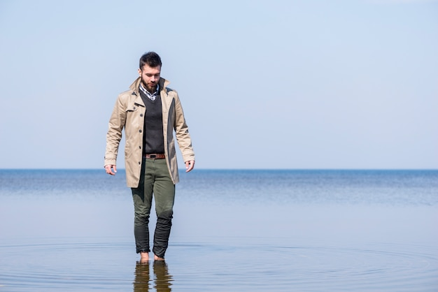 Stylish young man walking in the shallow sea water against blue sky Free Photo