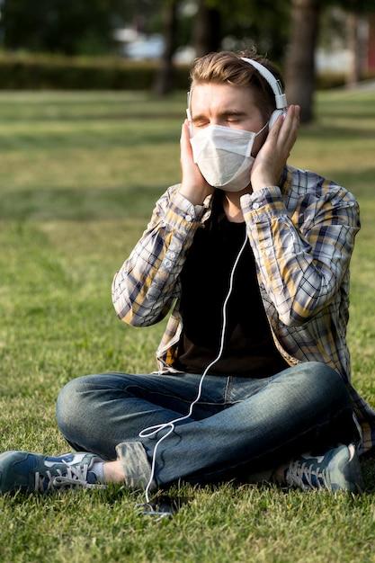 音楽を聞いてフェイスマスクとスタイリッシュな若い男 無料写真