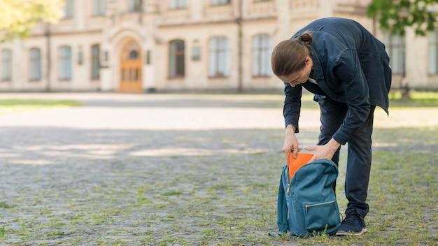 Стильная молодая студентка расставляет свой рюкзак Бесплатные Фотографии