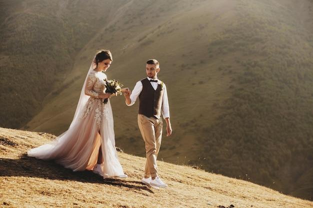 Stylish young wedding couple has fun posing in beautiful georgian mountains Premium Photo