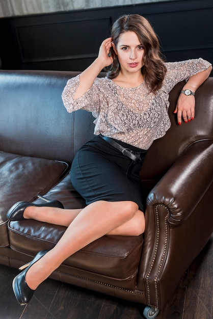Stylish young woman in black high heels sitting on brown sofa Free Photo